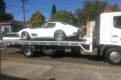 Tilt tray truck transport of white car