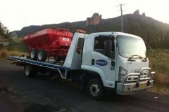 Tilt tray truck transporting an industrial equipment