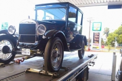 Classic vintage car towing by tilt tray truck